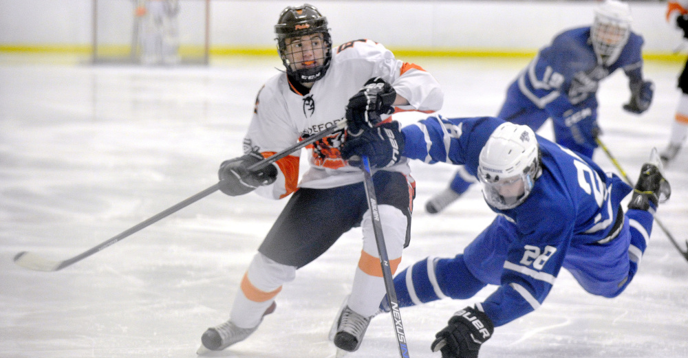 Max Mourmouras of Biddeford avoids a check from Nate Jewett of Kennebunk and sends the puck up the ice Monday during Biddeford's 7-2 victory at Biddeford Ice Arena. The Tigers improved their record to 4-3 and droped Kennebunk to 3-4-1.