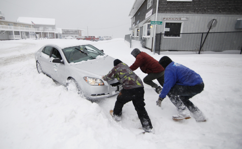 Nick Buonanno, Braden Haskell and Kurt Wenzel help a motorist whose car became stuck in a snowbank at Mile Road and Church Street in Wells during the season's first snow. The Dec. 29 storm is the second-latest snowfall in Portland's history; the record is Jan. 16, 2000.