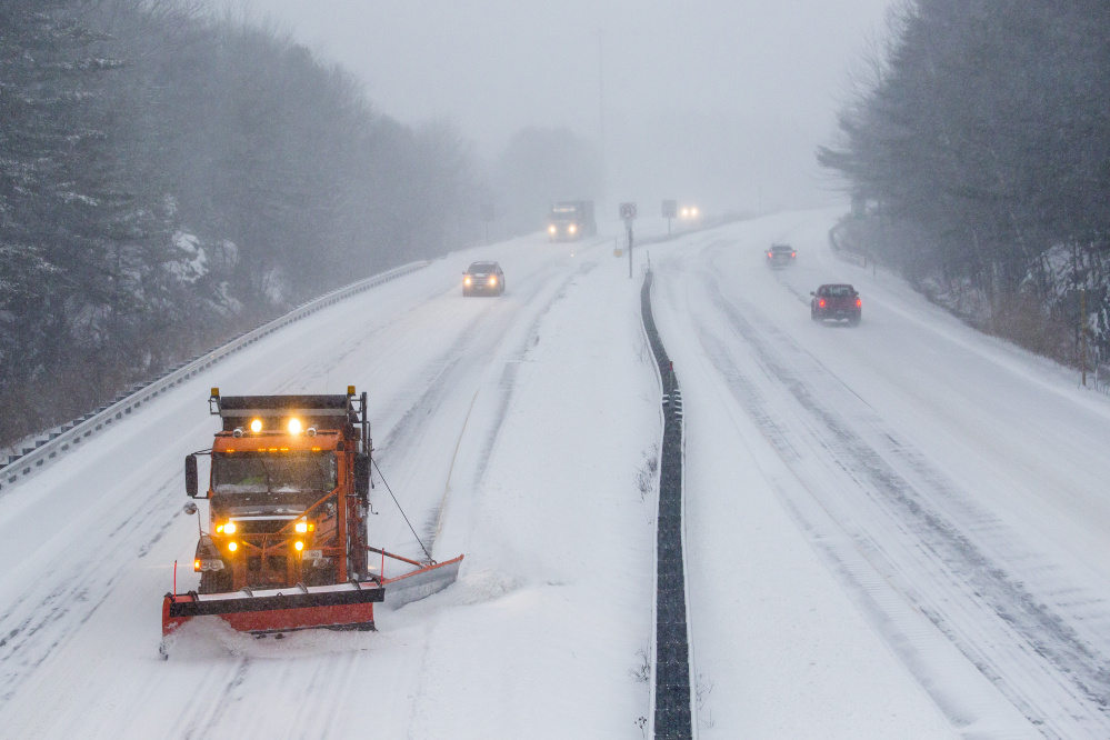 A plow truck clears the westbound lane of the Maine Turnpike spur in Falmouth as cars head into Portland during the morning commute in December 2015.