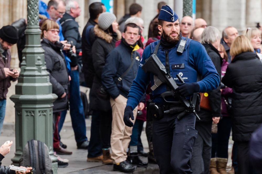 An armed officer patrols at the Grand Place in Brussels on Tuesday. Two people have been arrested in Belgium on suspicion of planning attacks in Brussels during the holidays, the federal prosecutor's office said.