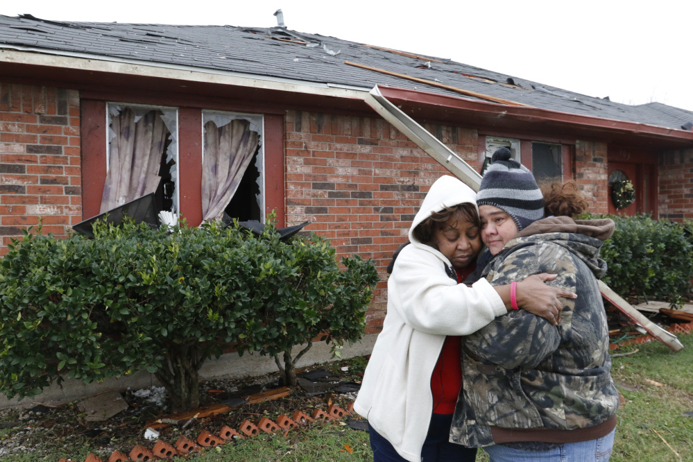 Roberta Moses, left, and Monica Holman embrace in Glenn Heights, Texas, on Monday.