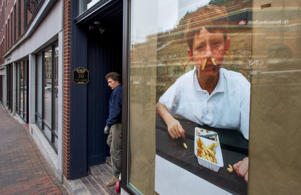 Sam Hopkins of MJ Plumbing & Heating walks past a large poster of a boy with french fries shoved in his ears and nose pasted in the window of what will be Hero, a sandwich shop at 30 City Center.