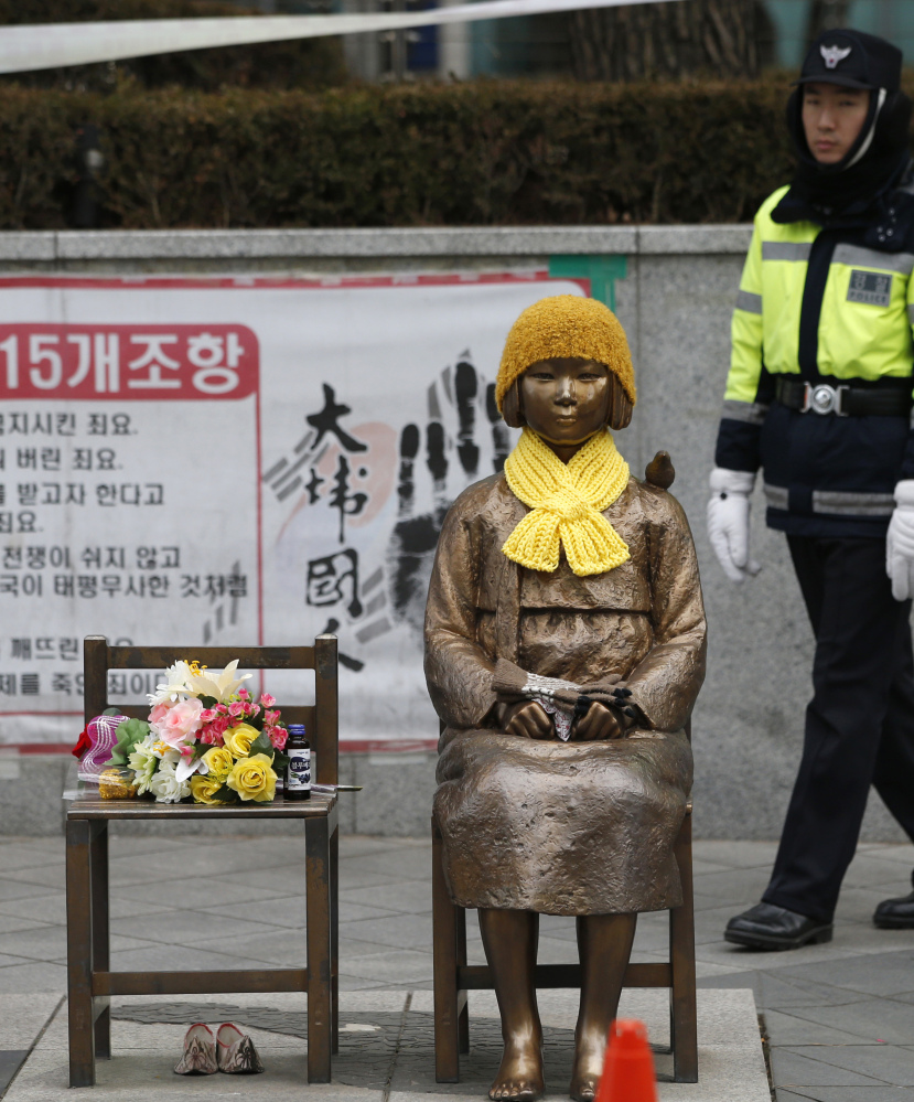 A South Korean police officer looks at the statue of a girl representing victims of Japanese sexual slavery in front of the Japanese Embassy in Seoul. Japan wants the statue removed while South Korea says it should stay.