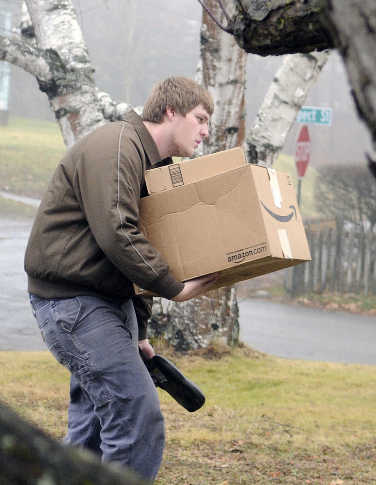 UPS driver helper Taylor Saulnier delivers a bundle of packages in Gardiner on Dec. 23.