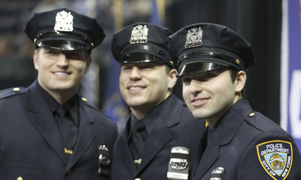 Brothers Stephan, left, John, center, and Alec Favale pose before the New York City Police Department Police Academy graduation ceremony Tuesday.