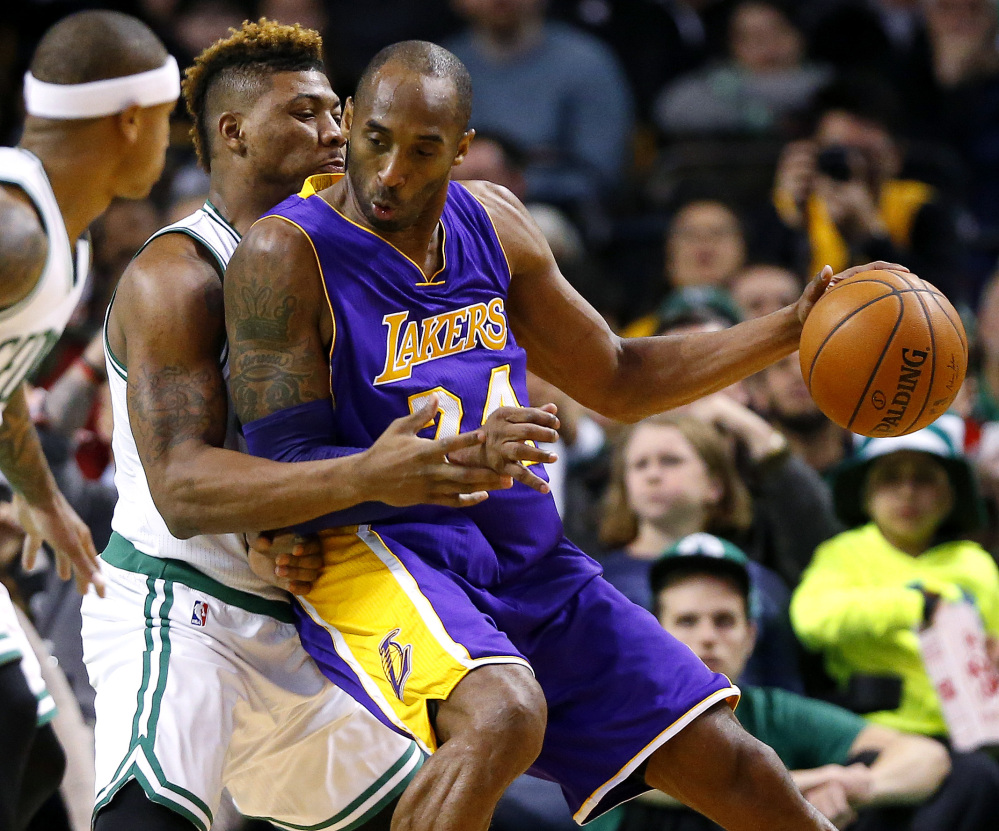 Los Angeles Lakers' Kobe Bryant moves on Boston Celtics' Marcus Smart during the second quarter of an NBA basketball game in Boston on Wednesday, Dec. 30, 2015. (AP Photo/Winslow Townson)