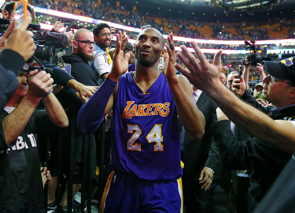 Kobe Bryant acknowledges the fans as he walks off the TD Garden court after the Lakers' 112-104 win over the Celtics in his last game in Boston.