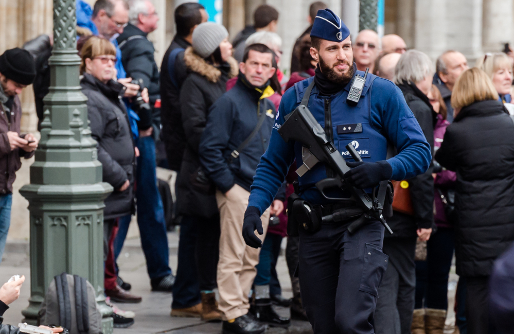 An armed officer patrols at the Grand Place in Brussels on Tuesday after two people were arrested on suspicion of planning attacks during the holidays.
