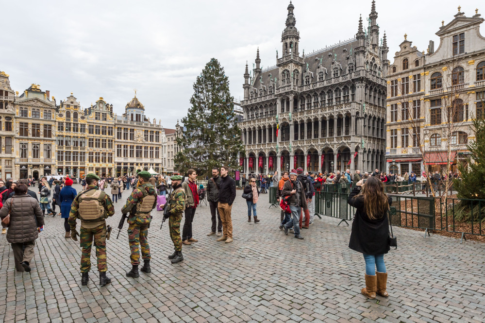 Belgian soldiers patrol as tourists visit the Grand Place in Brussels on Tuesday. The Belgian capital's main square, thronged this time of year with holiday shoppers and strollers, was one of the targets in a suspected new terror plot.