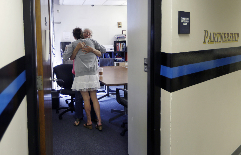 Kylee Moriarty, facing away, hugs volunteer Ruth Cote in the police station in Gloucester, Mass. In July, Moriarty became one of the first to benefit from the Gloucester Police Department's policy of helping addicts get treatment instead of jailing them.