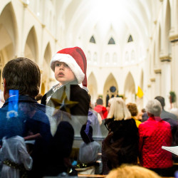 William Beebe, 5, of Westport, Conn., looks festive Thursday evening in the arms of his grandfather, Robert Beebe of Portland, at Christmas Eve Mass at Portland's Cathedral of the Immaculate Conception. The cathedral was packed for the Mass, with standing room only.