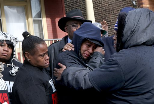 Janet Cooksey, center, the mother of Quintonio LeGrier, is comforted by family and friends during a Sunday news conference to speak out about Saturday's shooting death of her son by the Chicago police. Nancy Stone/Chicago Tribune via AP