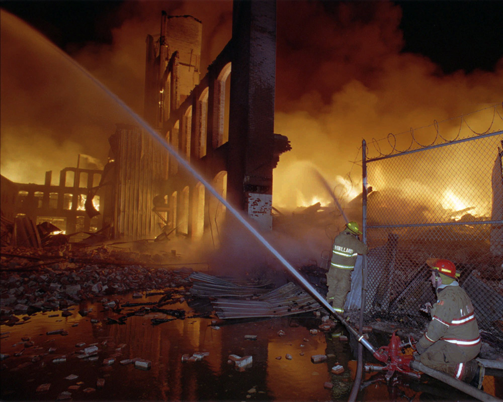 Firefighters pour water onto the burning Malden Mills plant in this Dec. 11, 1995, photo. Thirty-one workers were injured in the fire and explosions, eight critically, according to the state fire marshal. The Associated Press