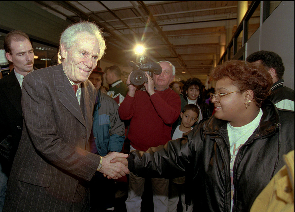 Aaron Feuerstein, then-president and owner of Malden Mills Industries Inc. shakes hands with workers in Lawrence, Mass., in this  Jan. 11, 1996, photo, after he assured them of an extension of their wage and benefit packages for at least another 30 days. An estimated 1,800 workers at the textile mill were left jobless by a December 1995 fire that destroyed several buildings. The Associated Press