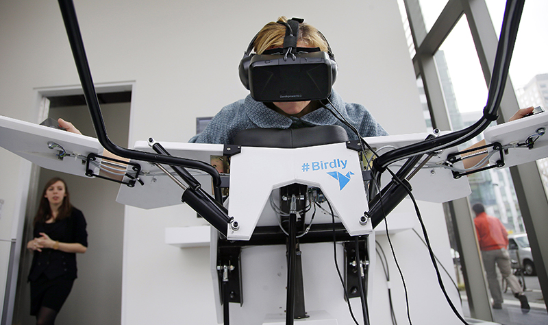 Birdly looks like a futuristic examining table where users lie on their bellies and spread their arms like wings. Using virtual reality goggles, they get a bird's eye view of New York City. By rotating their hands and flapping their arms, they navigate the skyline.