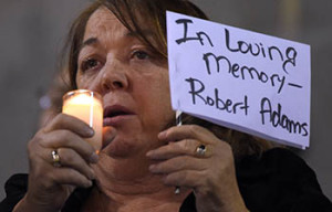 A woman holds a sign for Robert Adams, who died in a shooting on Wednesday, during a vigil for shooting victims on Thursday, Dec. 3, 2015, at San Manuel Stadium in San Bernardino, Calif. A husband and wife opened fire on a holiday banquet, killing multiple people on Wednesday. Hours later, the couple died in a shootout with police. (AP Photo/Mark J. Terrill)