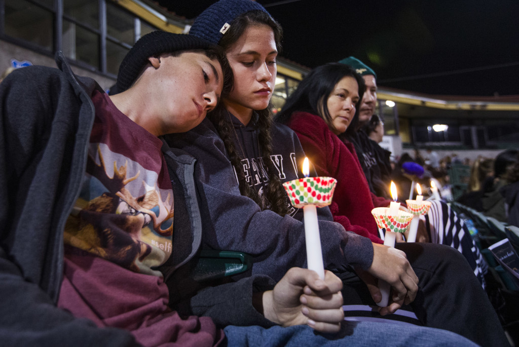 The McIntyre family from Redlands, Calif., hold candles at a vigil Thursday, in remembrance of the 14 people killed Wednesday in the San Bernardino mass shooting. The parents are middle school teachers. Tom Tingle/The Arizona Republic via AP