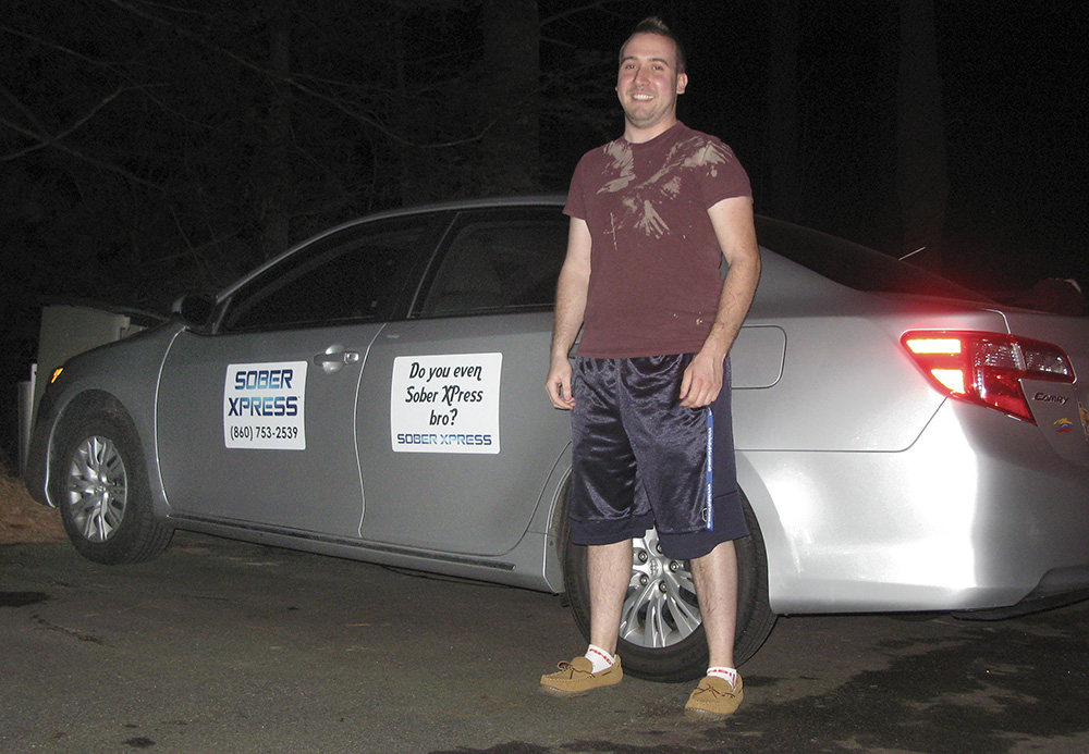 Lance Graziano, 22, with one of the rcars one his Willington, Conn., company uses to provide rides to drunk UConn students on the weekends. The Associated Press