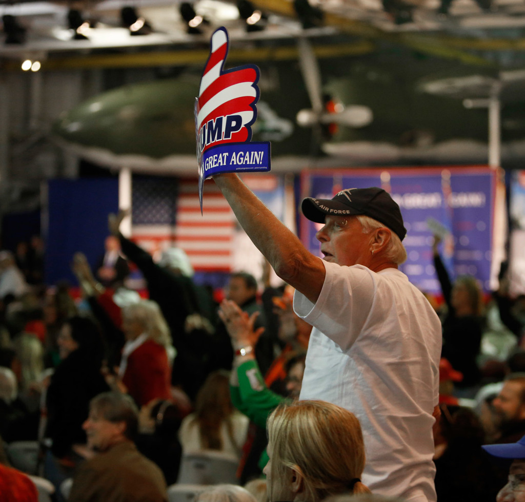 Supporters of Donald Trump wave to the press after being prodded by Trump during a rally Monday night aboard the aircraft carrier USS Yorktown in Mt. Pleasant, S.C. The crowd cheered Trump's call for a ban on Muslims entering the U.S. The Associated Press