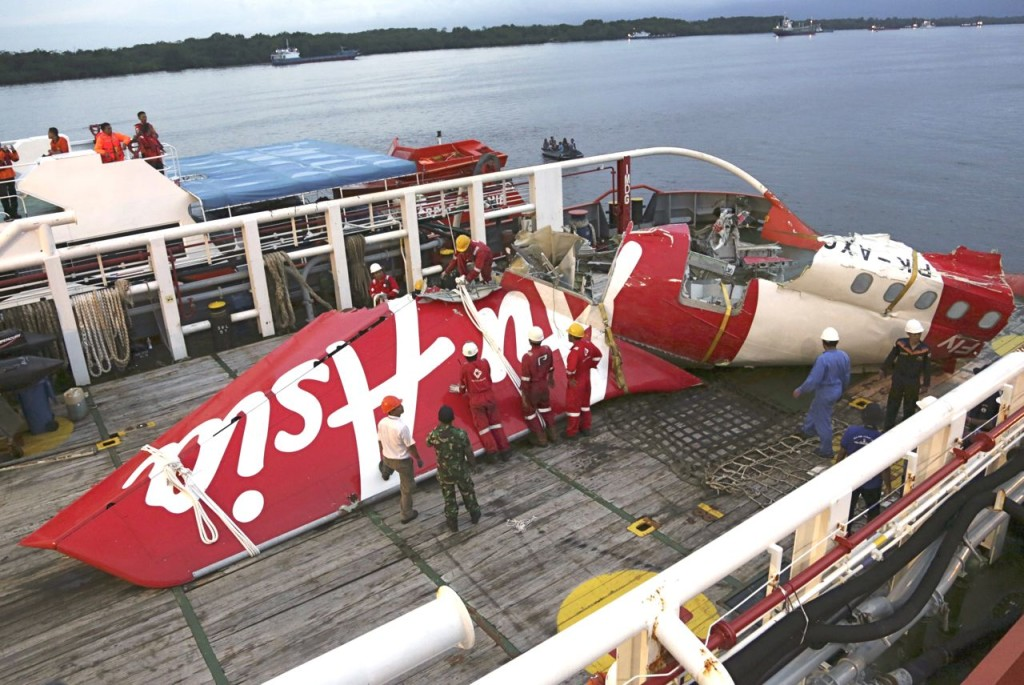 Crew members of a recovery ship prepare to unload the tail section of AirAsia Flight 8501 at Kumai port in Pangkalan Bun, Central Borneo, Indonesia, on Jan. 11. The National Transportation Safety Committee says an analysis of Flight 8501's data recorder showed that the Airbus A320 had problems with its rudder control system while flying between the Indonesian city of Surabaya and Singapore on Dec. 28. The Associated Press