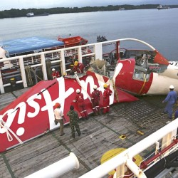 Crew members of a recovery ship prepare to unload the tail section of crashed AirAsia Flight 8501 at Kumai port in Pangkalan Bun, Central Borneo, Indonesia, on Jan. 11, 2015. The National Transportation Safety Committee says an analysis of Flight 8501's data recorder showed that the Airbus A320 had problems with its rudder control system while flying between the Indonesian city of Surabaya and Singapore on Dec. 28. The Associated Press