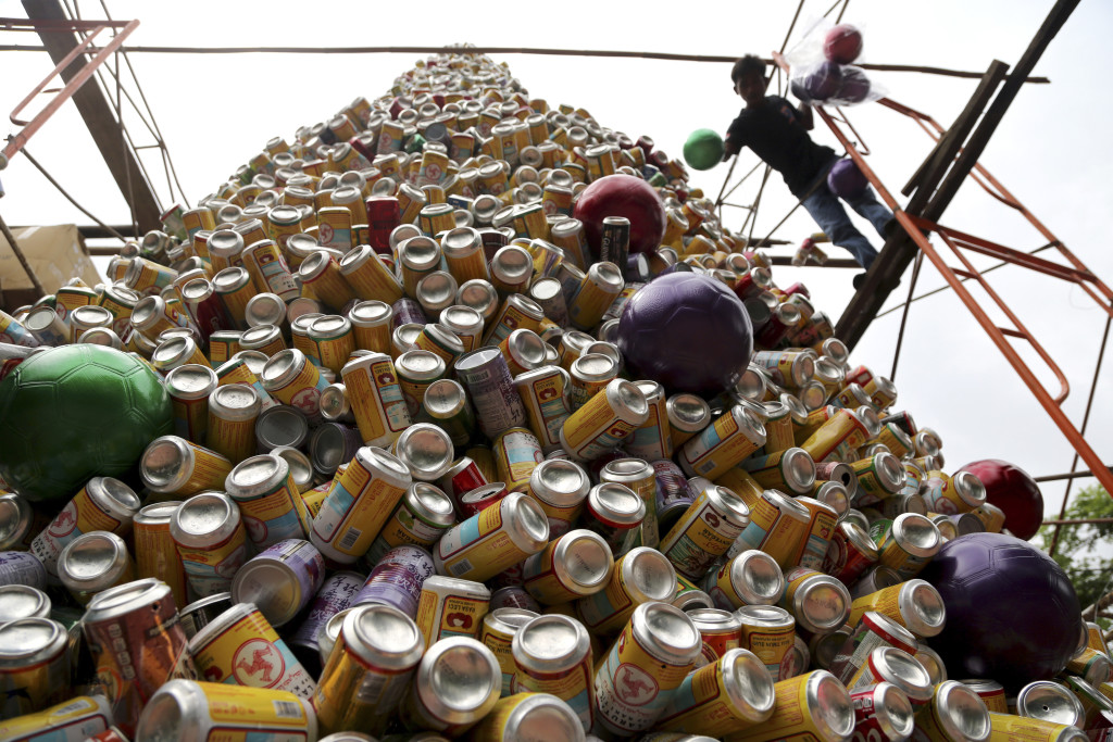 A worker arranges about 10,000 discarded beverage cans to form a Christmas tree in front of a church in Jakarta, Indonesia, Friday. Colored soccer balls are used as ornaments.