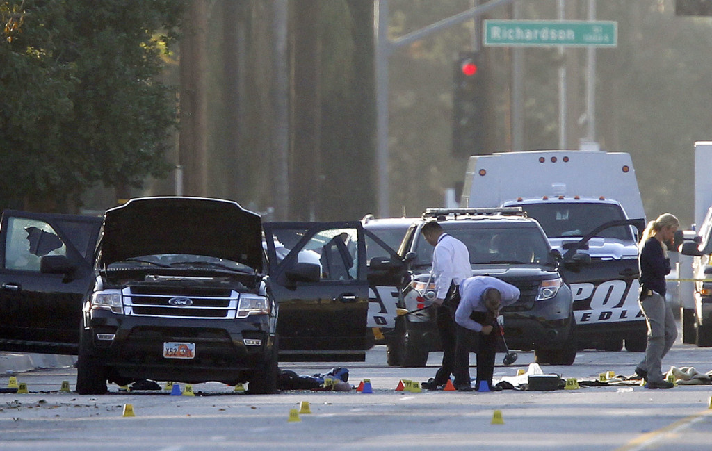 Investigators work Friday around the SUV where the two San Bernardino attackers were killed by police two days earlier. The FBI is investigating the massacre as an