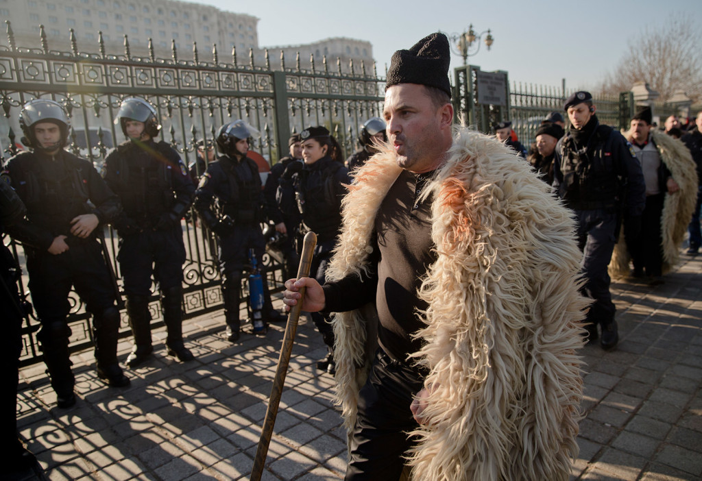 A shepherd whistles after breaking through riot police lines during a protest in Bucharest, Romania, on Tuesday. More than 1,000 angry shepherds broke through fences into the grounds of Romania's Parliament, scuffled with riot police who fired tear gas, to protest a law that regulates the number of sheepdogs they can use and bans them from grazing sheep during the winter.