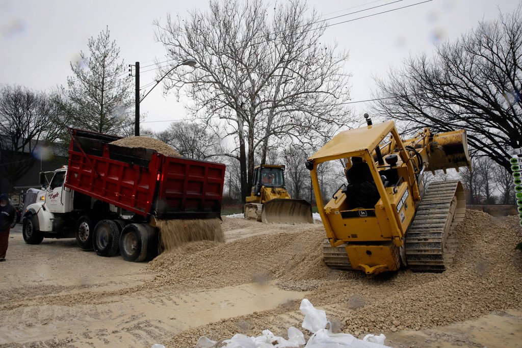 Heavy equipment is used to build a temporary levee to hold back floodwater in Kimmswick, Mo. Missouri Gov. Jay Nixon has declared a state of emergency due to widespread flooding around the state that has closed many roads.