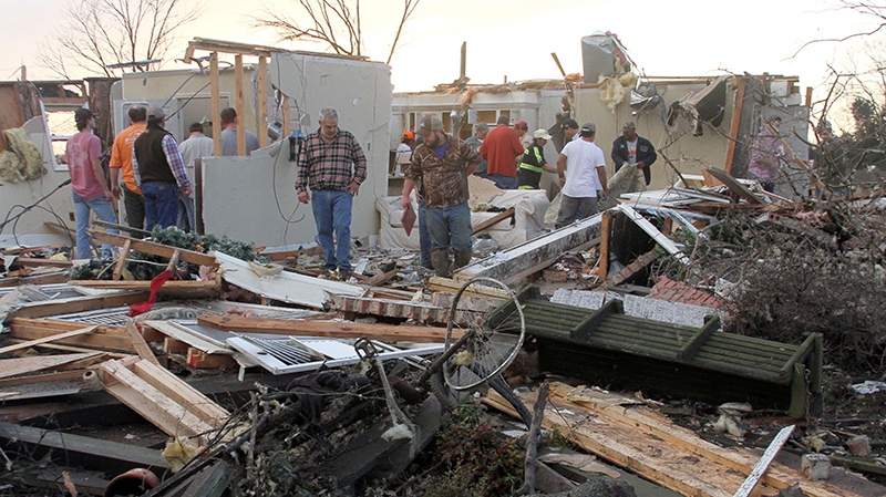 People inspect a storm-damaged house in Roundaway, Mississippi.