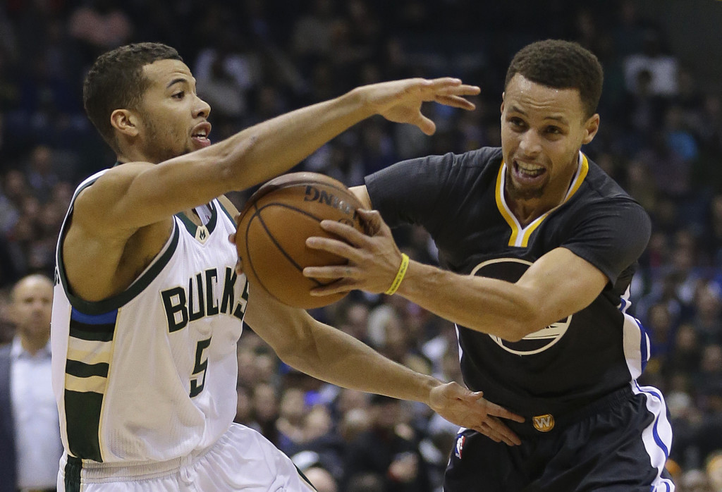 Stephen Curry, right, of the Golden State Warriors looks to drive against Michael Carter-Williams of the Milwaukee Bucks in the first half of Milwaukee's 108-95 victory Saturday night that sent Golden State to its first loss. The Associated Press