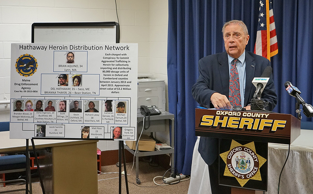 "Maine Department of Public Safety Commissioner John Morris speaks at a news conference announcing the ""largest drug investigation in Oxford County history."" Next to him is a poster charting those who have been arrested."