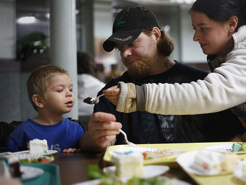 Amanda Proctor and her boyfriend Chris Swan, both of Lewiston, watch as their son Christopher Swan , 4, takes a bite of cake at a City Mission meal at Calvary United Methodist Church.