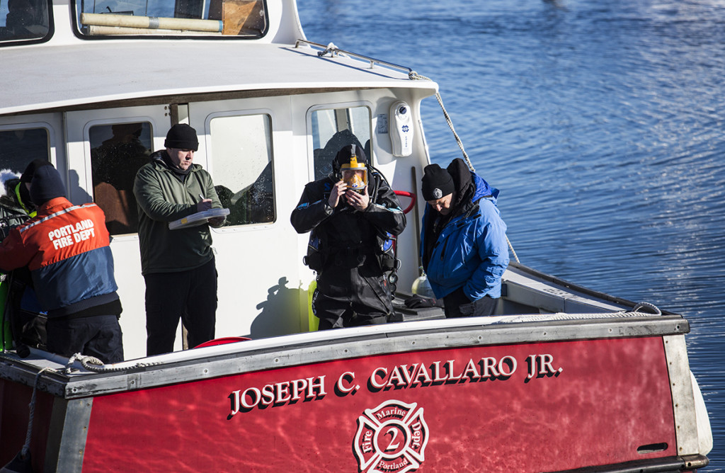Support personnel assist divers searching the waters for James Dyer near Union Wharf on Tuesday. Whitney Hayward/Staff Photographer