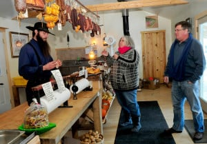 Matt Secich offers samples of his variety of smoked meats and cheeses to customers Sally and Chris Waterhouse at the shop in Unity on Wednesday. David Leaming/Morning Sentinel