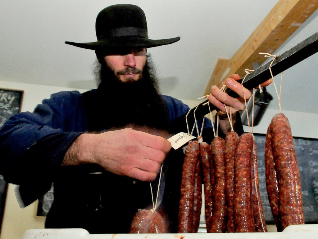 Matt Secich hangs sausages on a bar to dry at his Charcuterie shop in Unity on Wednesday. David Leaming/Morning Sentinel