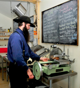 Matt Secich uses a hand-powered slicer to cut bacon at his Charcuterie shop. David Leaming/Staff Photographer