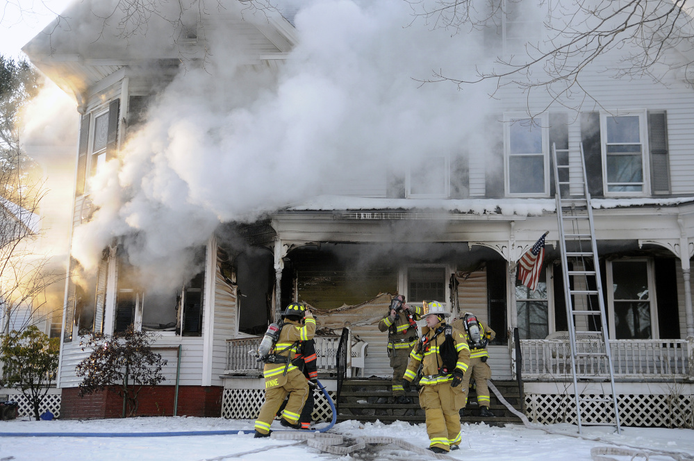 Firefighters scramble to contain a blaze Wednesday inside a residence on 37 Riverview Drive in Gardiner. The home was heavily damaged by fire and smoke, firefighters said.