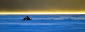 Snowmobilers speed across Rangeley Lake ahead of the start of the annual Snowdeo on Thursday.