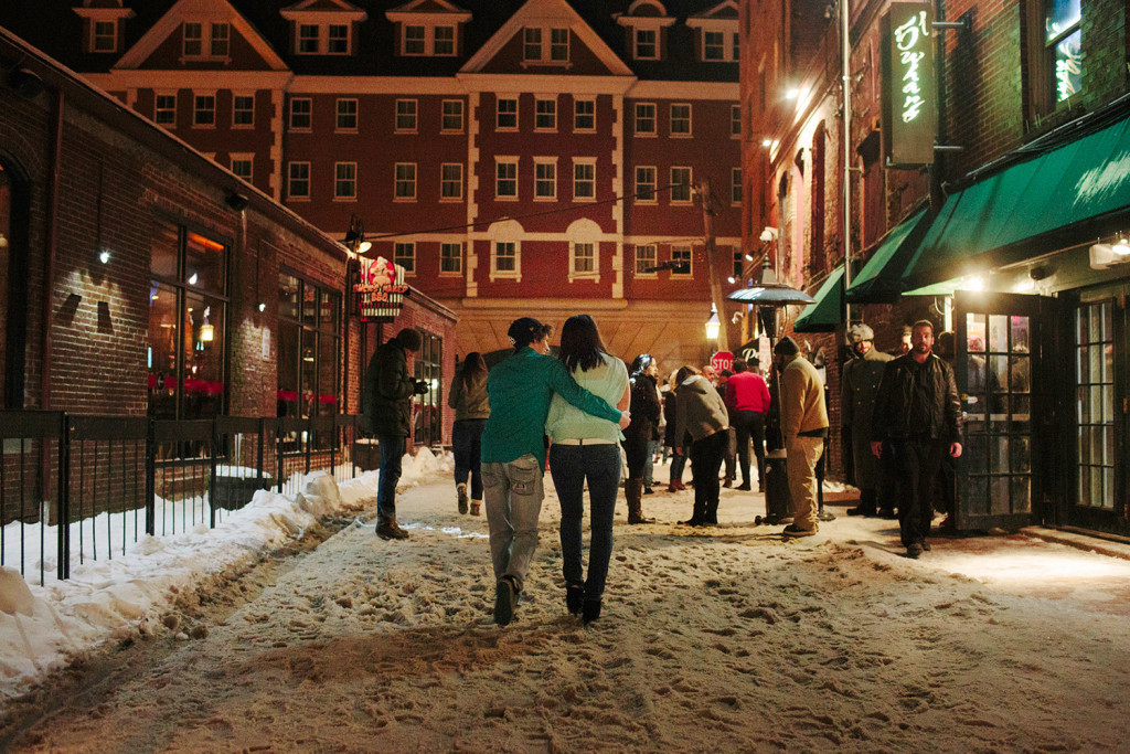 Patrons of bars and nightclubs along Wharf Street in Portland walk outside after bars close at 1 a.m., with the Portland Harbor Hotel in the background. A group is trying to find a compromise between the popular nightclubs and nearby hotels, whose patrons often complain about noise.