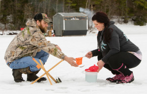 A shiner escapes in the exchange from Lacey Lang to her boyfriend, Tim Hansen, while they ice fish Tuesday on Pequawket Pond in Limington. Lang said she won't fish on ice that's less than 6 to 8 inches thick. Carl D. Walsh/Staff Photographer