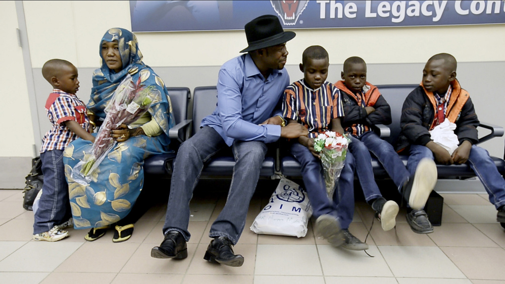 Haroun Adam sits with his wife, Mariam, and family at the Portland International Jetport after they arrived on Dec. 17. His children, from left, are 4-year-old Maaz, 9-year-old twins Motasim and Mohamed and Mortada, 6.