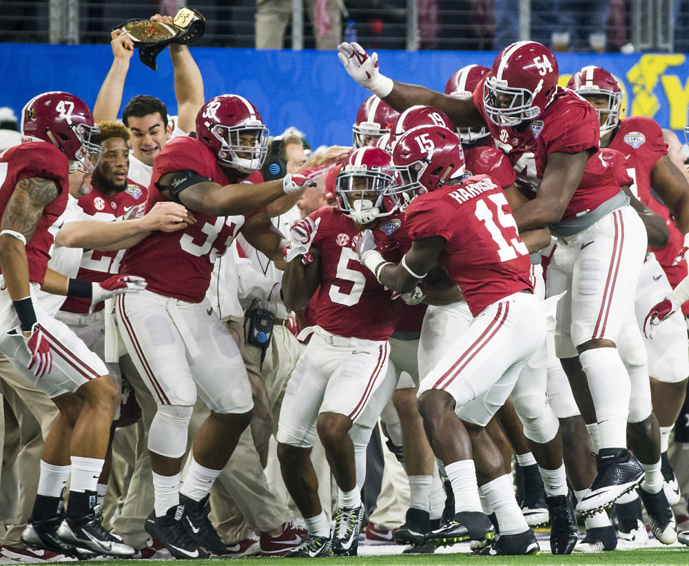 Alabama defensive back Cyrus Jones (5) is mobbed by teammates after intercepting a pass in the Cotton Bowl.
