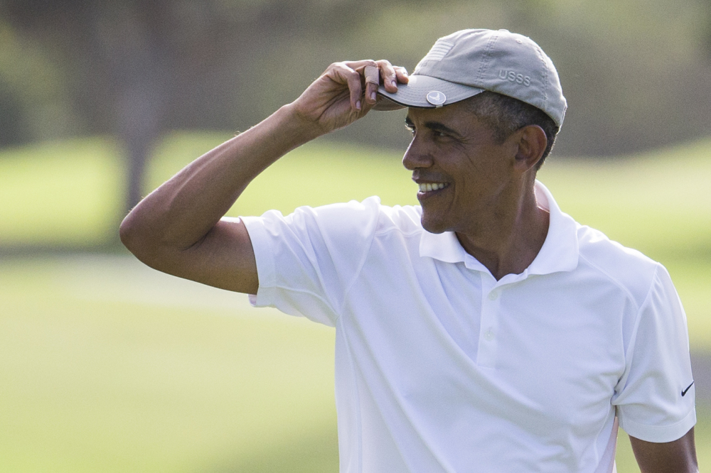 President Barack Obama tips his hat to the crowd after finishing a round of golf at Mid-Pacific Country Club during his family vacation on Monday in Kailua, Hawaii.