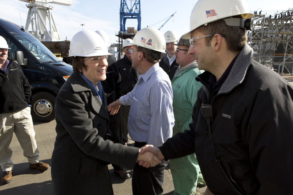 U.S. Sen. Susan Collins greets Bath Iron Works supervisor Chris Comora during a 2013 tour of the shipbuilding plant. A reader says the senator has manipulated the national budget to fund a Navy destroyer.