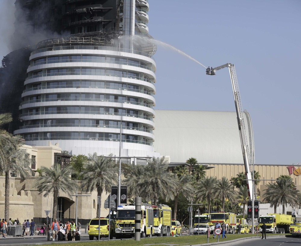 Firefighters spray water on a fire burning in the Address Downtown skyscraper in Dubai, United Arab Emirates, on Friday. The blaze's cause is under investigation.