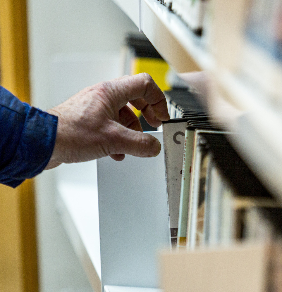 A man grabs a DVD from a shelf at the Portland Public Library. Videoport donated 18,000 titles after closing its Old Port store in August.