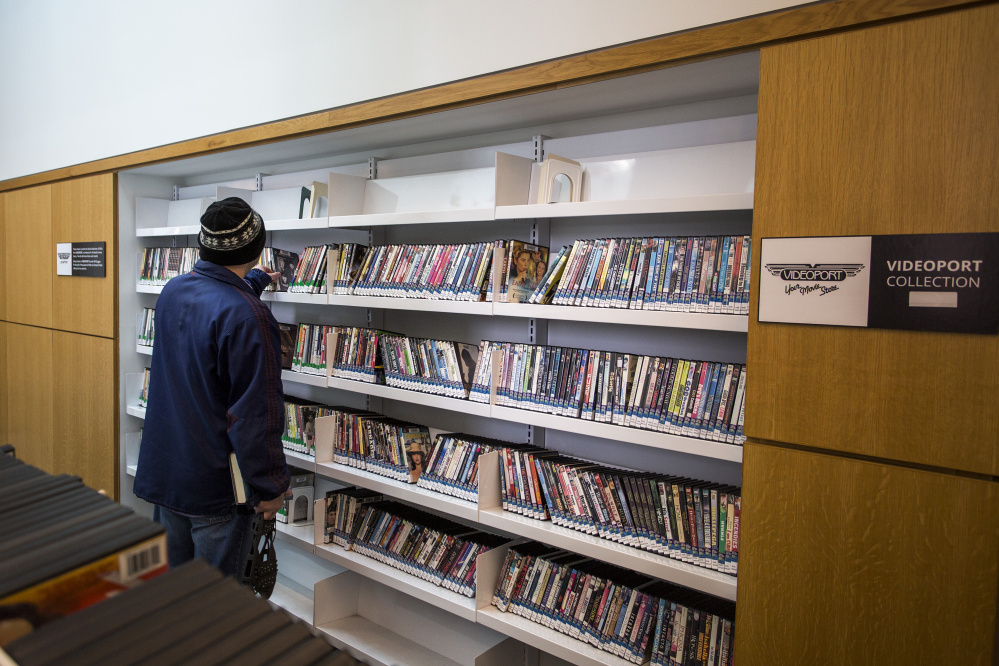 "Cory Legassie of Portland looks at DVDs donated to the Portland Public Library by Videoport, the Old Port video store that went out of business in August after 28 years. ""I miss Videoport, so it's good to seem them back in some form or another,"" he said."