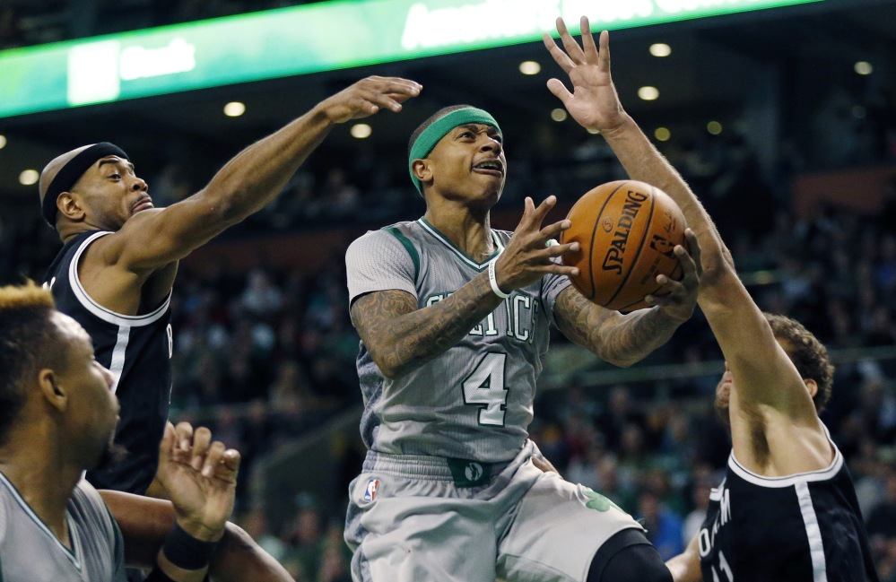 Boston's Isaiah Thomas goes up to shoot between Brooklyn's Jarrett Jack, left, and Brook Lopez, right, during the Nets' 100-97 win Saturday in Boston.