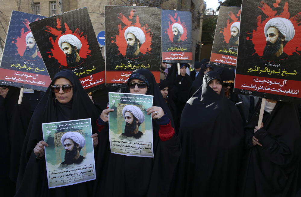 Iranians hold posters of Sheikh Nimr Baqr al-Nimr, a prominent Shiite cleric, during a protest denouncing his execution, in front of the Saudi embassy in Tehran on Sunday. Saudi Arabia executed 47 people, mostly al-Qaida suspects, Saturday.